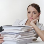 A stressed female, sitting at her desk with a large pile of papers stack in front of her